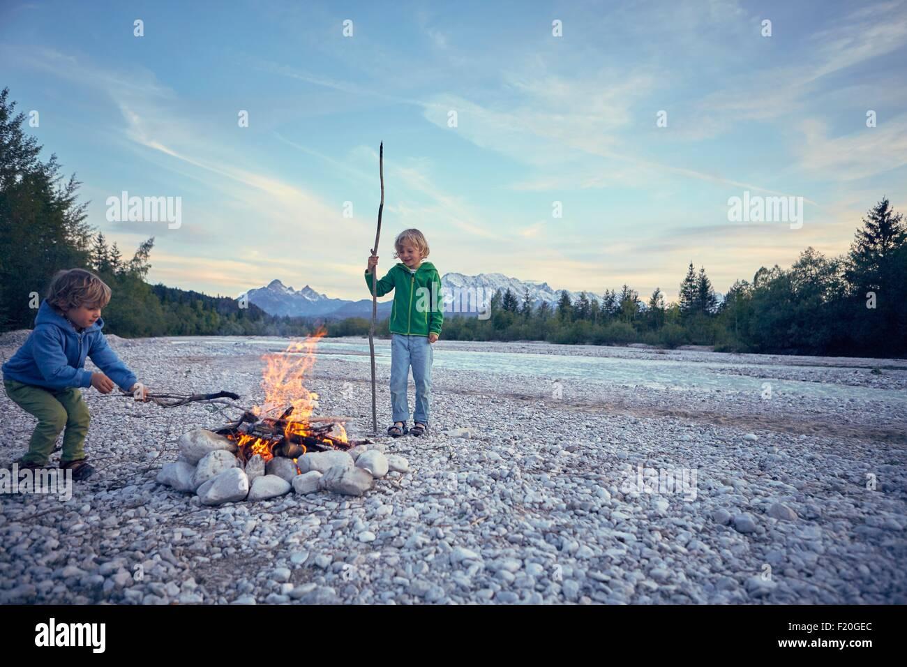 Los muchachos metiendo fogata con palos, Wallgau, Baviera, Alemania Imagen De Stock