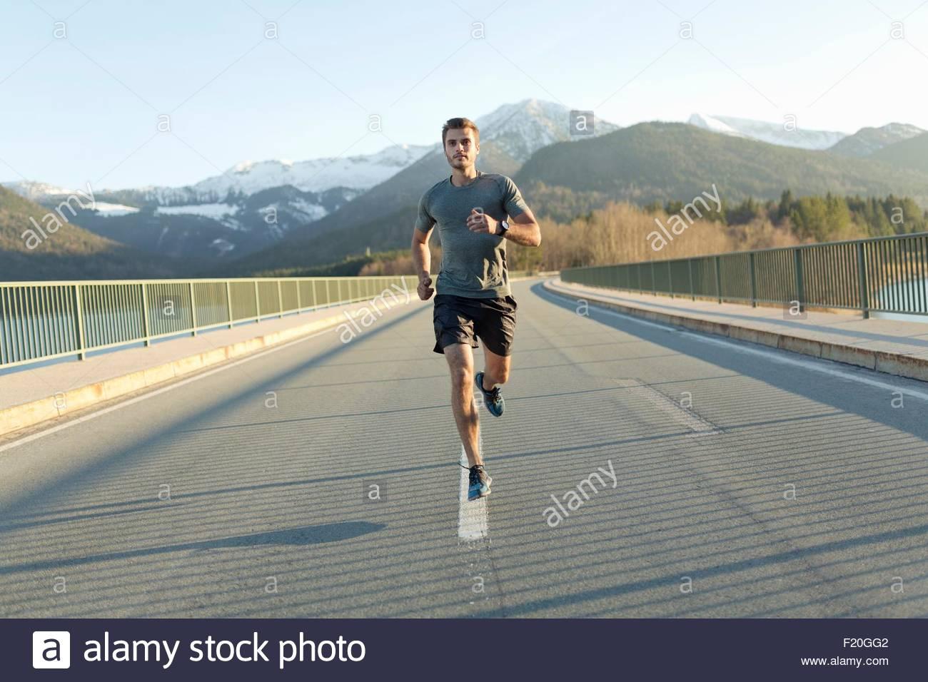Joven, corriendo en la carretera, las montañas detrás de él, vista frontal Imagen De Stock