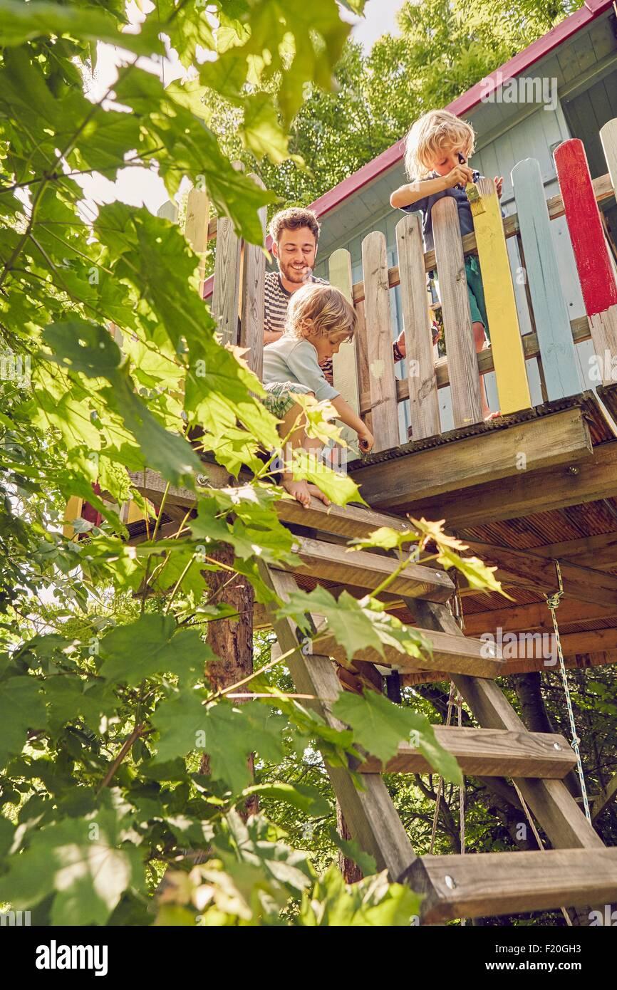 Padre y sus dos hijos, pintura de casa en el árbol, bajo ángulo de visión Imagen De Stock