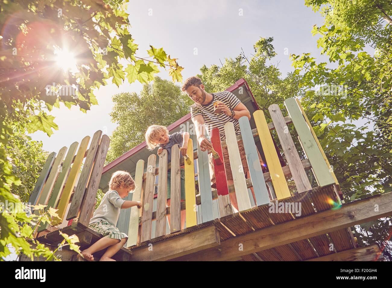 Padre y sus dos hijos, pintura de casa en el árbol, bajo ángulo de visión Foto de stock