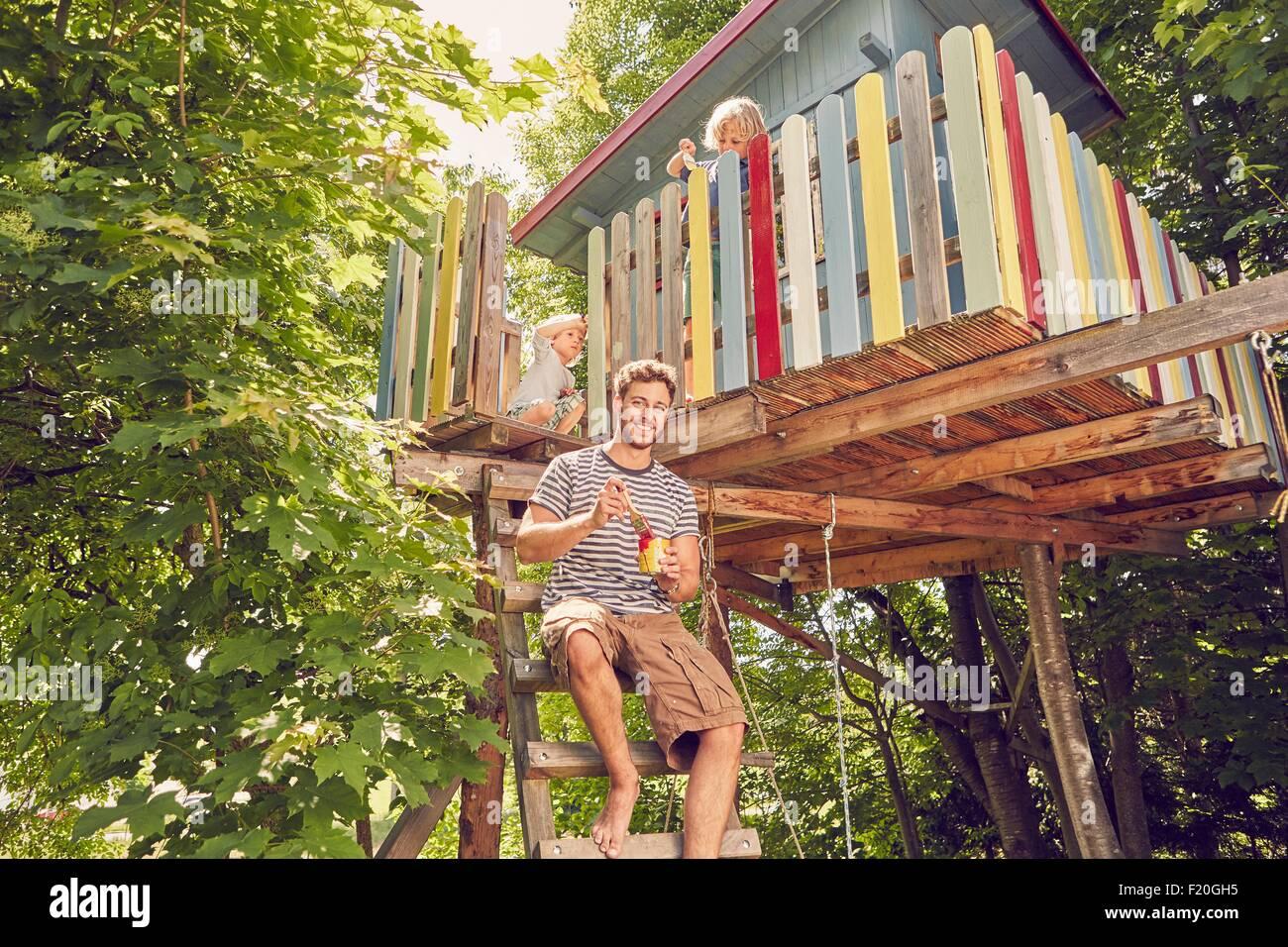Retrato del padre y los dos hijos de pintar una casa en el árbol Imagen De Stock