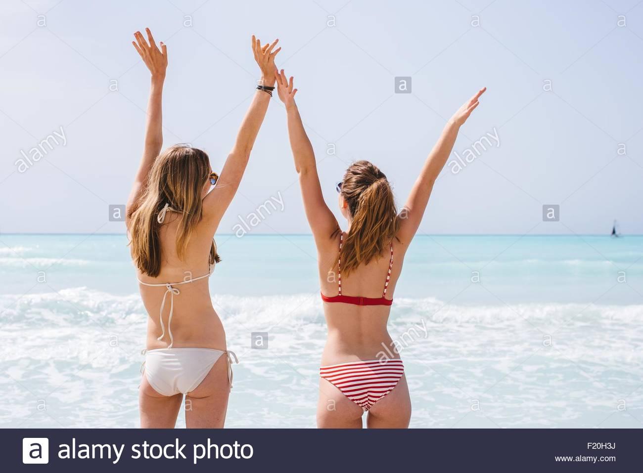 Vista trasera de dos amigas jóvenes luciendo bikinis con los brazos levantados en la playa Imagen De Stock