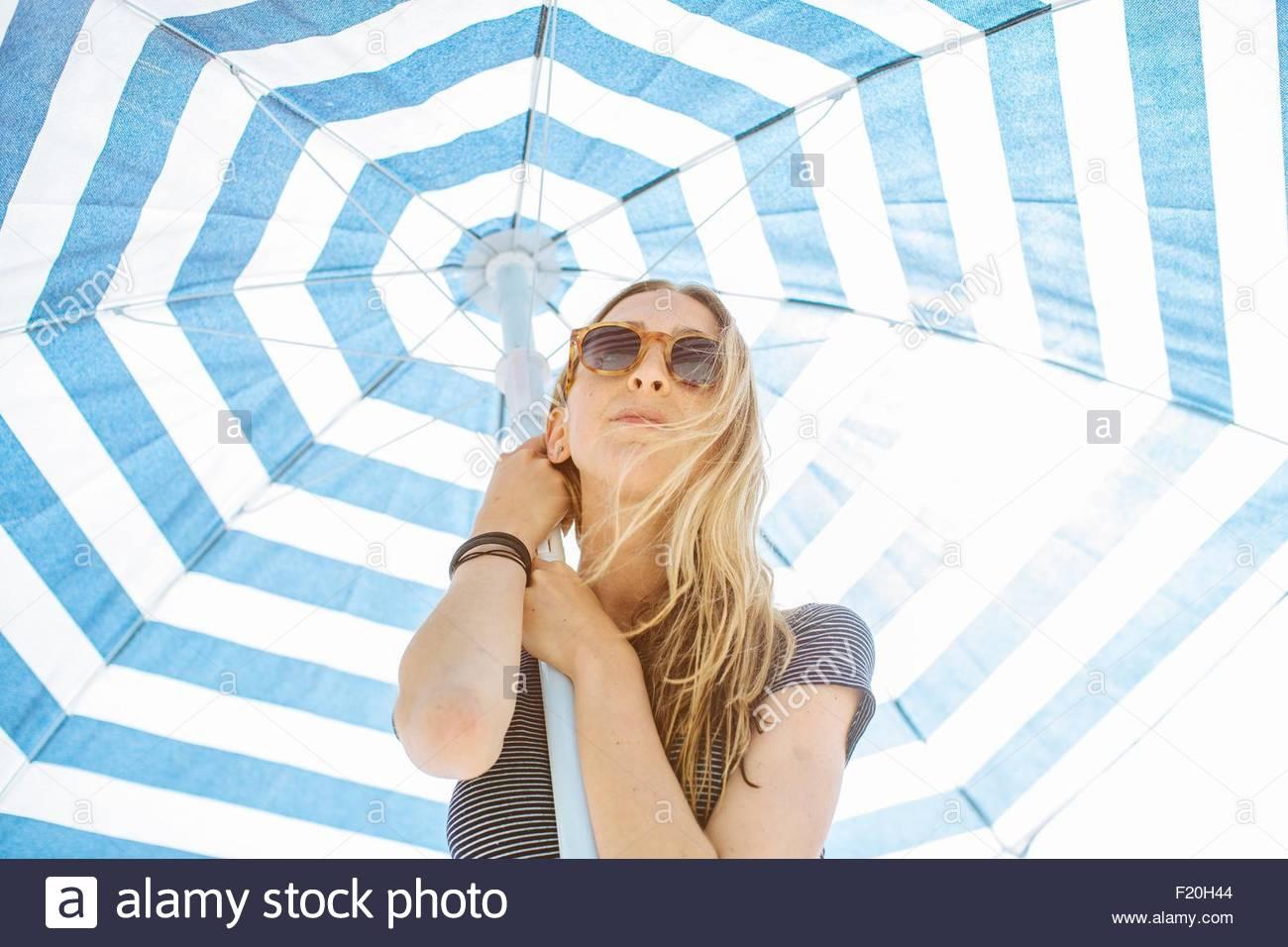 Un ángulo bajo el retrato de mujer joven mantiene sombrilla rayas Imagen De Stock