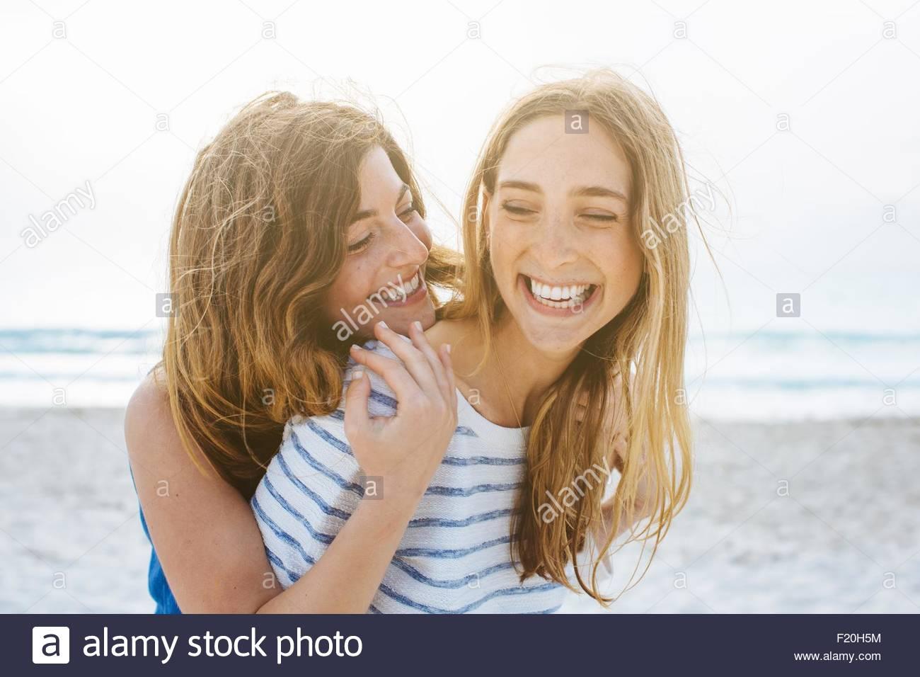 Dos amigas jóvenes riendo en la playa Imagen De Stock