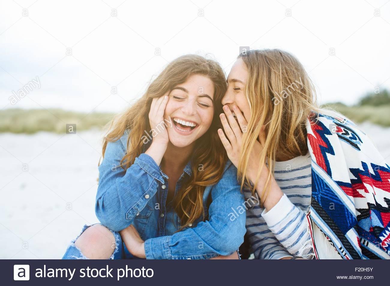 Dos amigas jóvenes susurrando en la playa Imagen De Stock