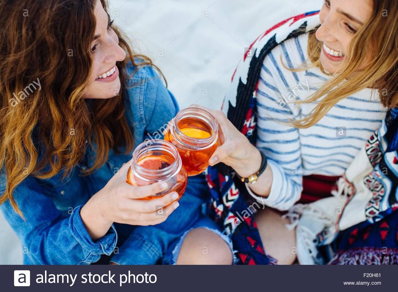 Dos amigas jóvenes brindando con jar beber en la playa Imagen De Stock