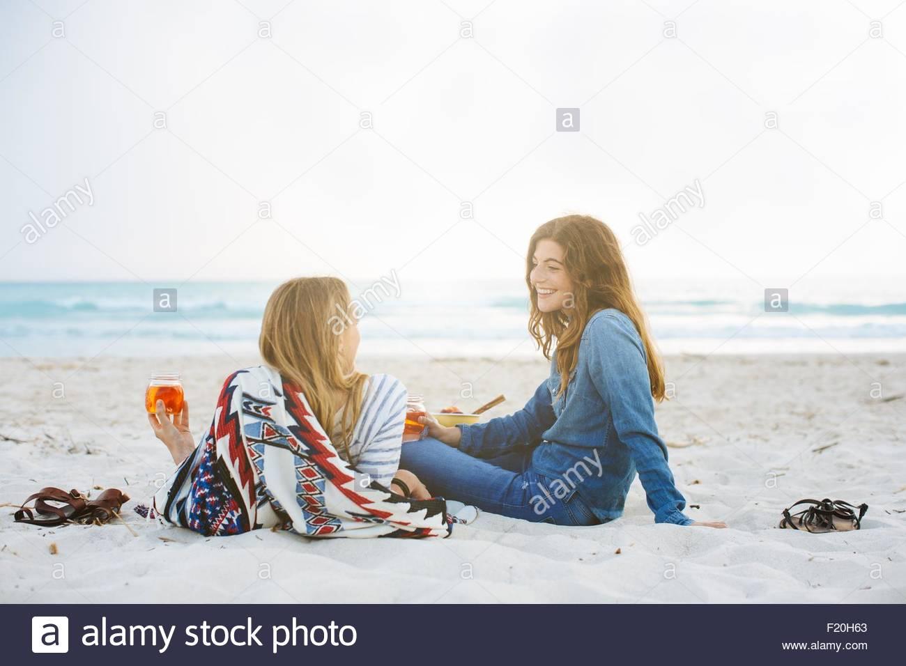 Dos amigas jóvenes reclinados con jar bebidas en la playa Imagen De Stock