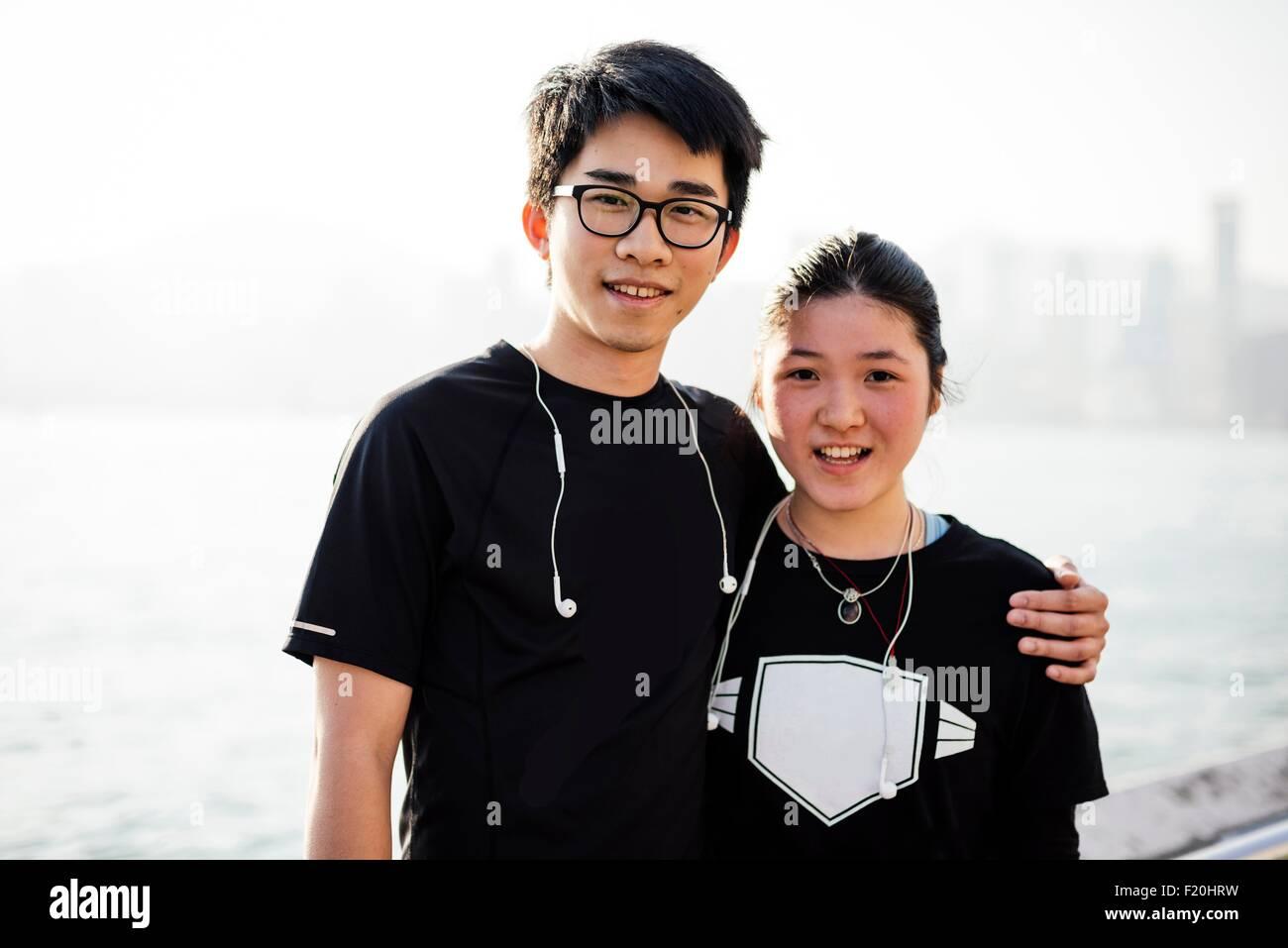 Retrato de joven con brazo alrededor de joven, vistiendo los auriculares, mirando a la cámara sonriendo Imagen De Stock