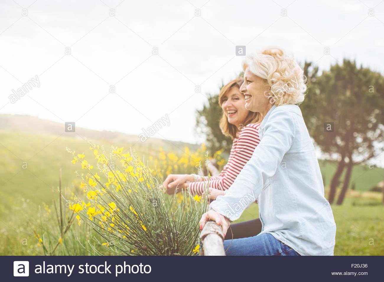 Dos amigos de hembras maduras apoyándose en valla, Toscana, Italia Imagen De Stock