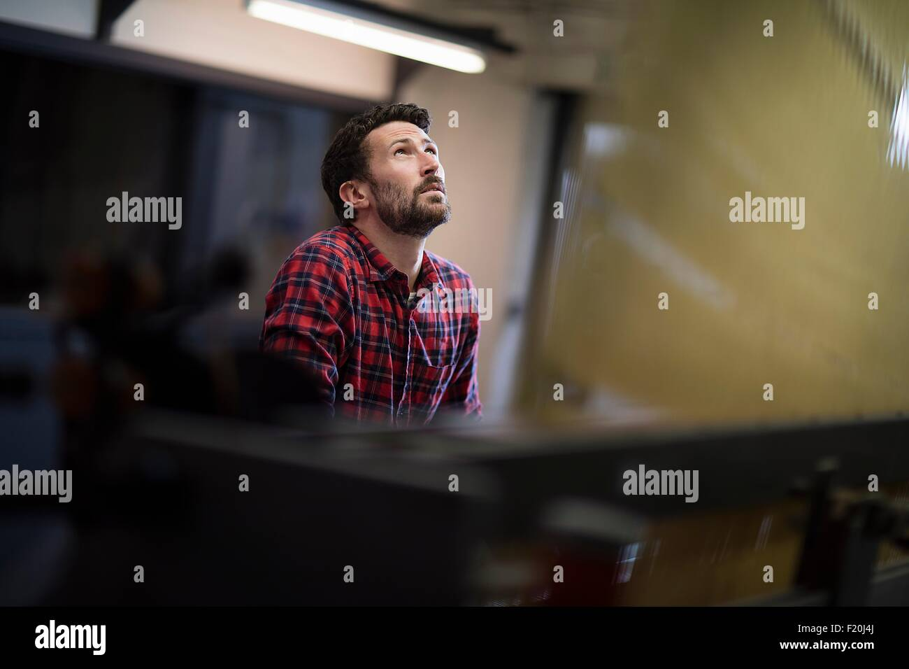 Macho joven weaver mirando a las roscas de la antigua fábrica de tejidos en telares Imagen De Stock