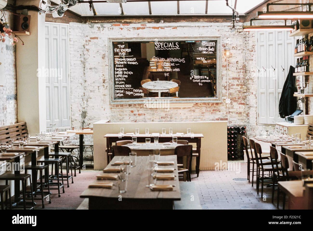 fef5aaba9946 Un restaurante con mesas y sillas largas y angostas establecidos para una  comida. Un gran menú Chalk board.