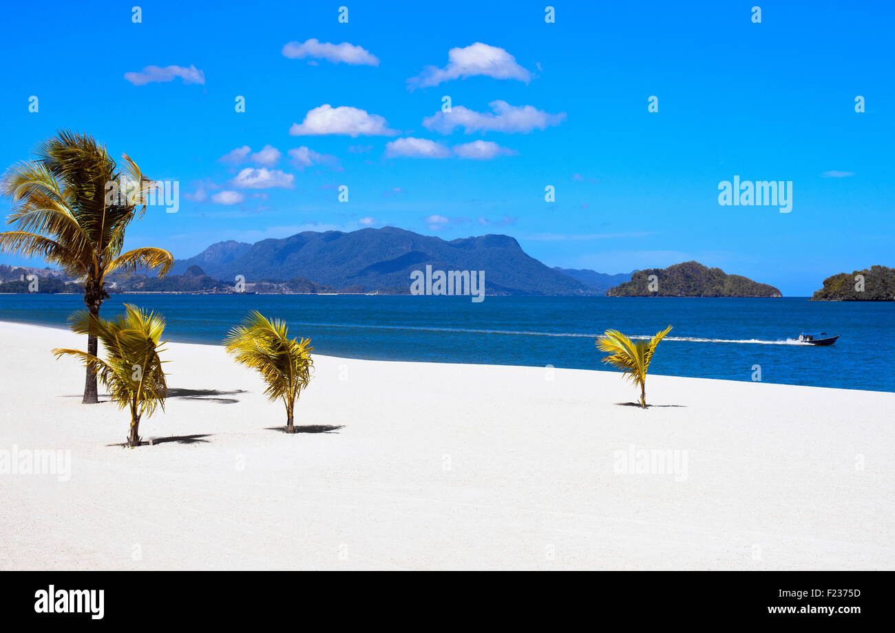 Un barco de motor velocidades a lo largo de la playa privada frente al Royal Villa en Four Seasons Langkawi, Malasia Imagen De Stock