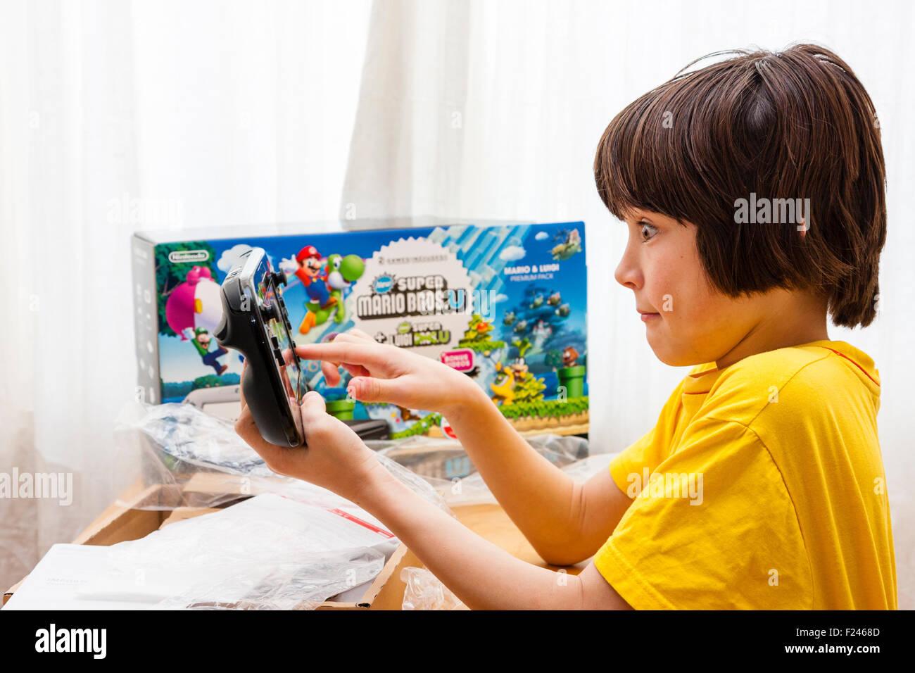 Hijo varón caucásico, muchacho, 11-13 años, sosteniendo en ambas manos una consola Nintendo Wii U justo después de sacarlo de la caja, que está junto a él. Foto de stock