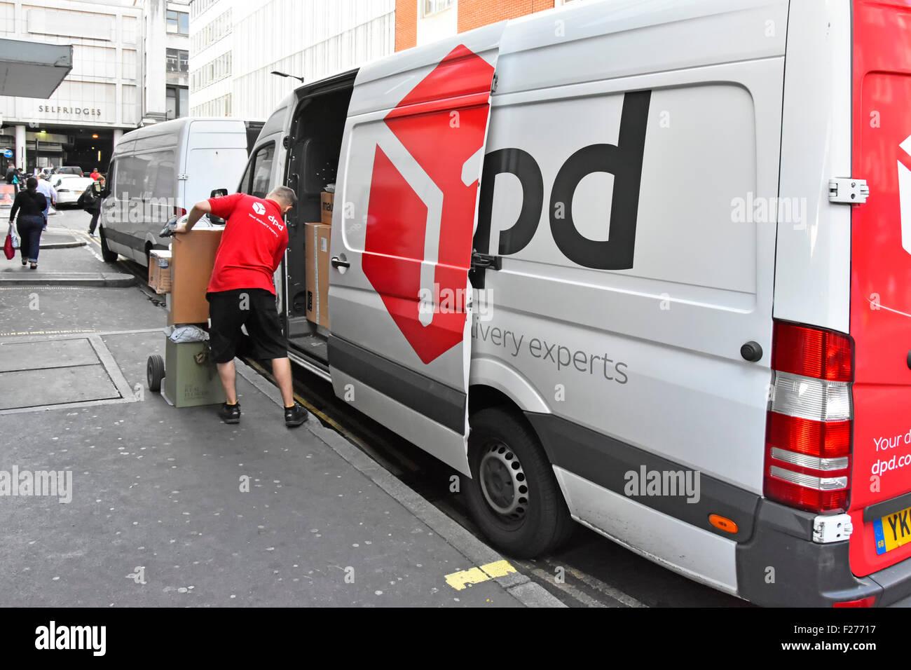 Controlador de entrega hombre cargando bultos en camilla de entrega DPD van Londres England Reino Unido Imagen De Stock