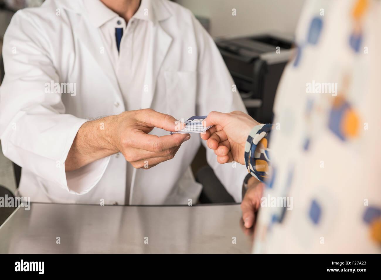 Paciente dando una tarjeta de seguro de salud al doctor, Munich, Baviera, Alemania Imagen De Stock