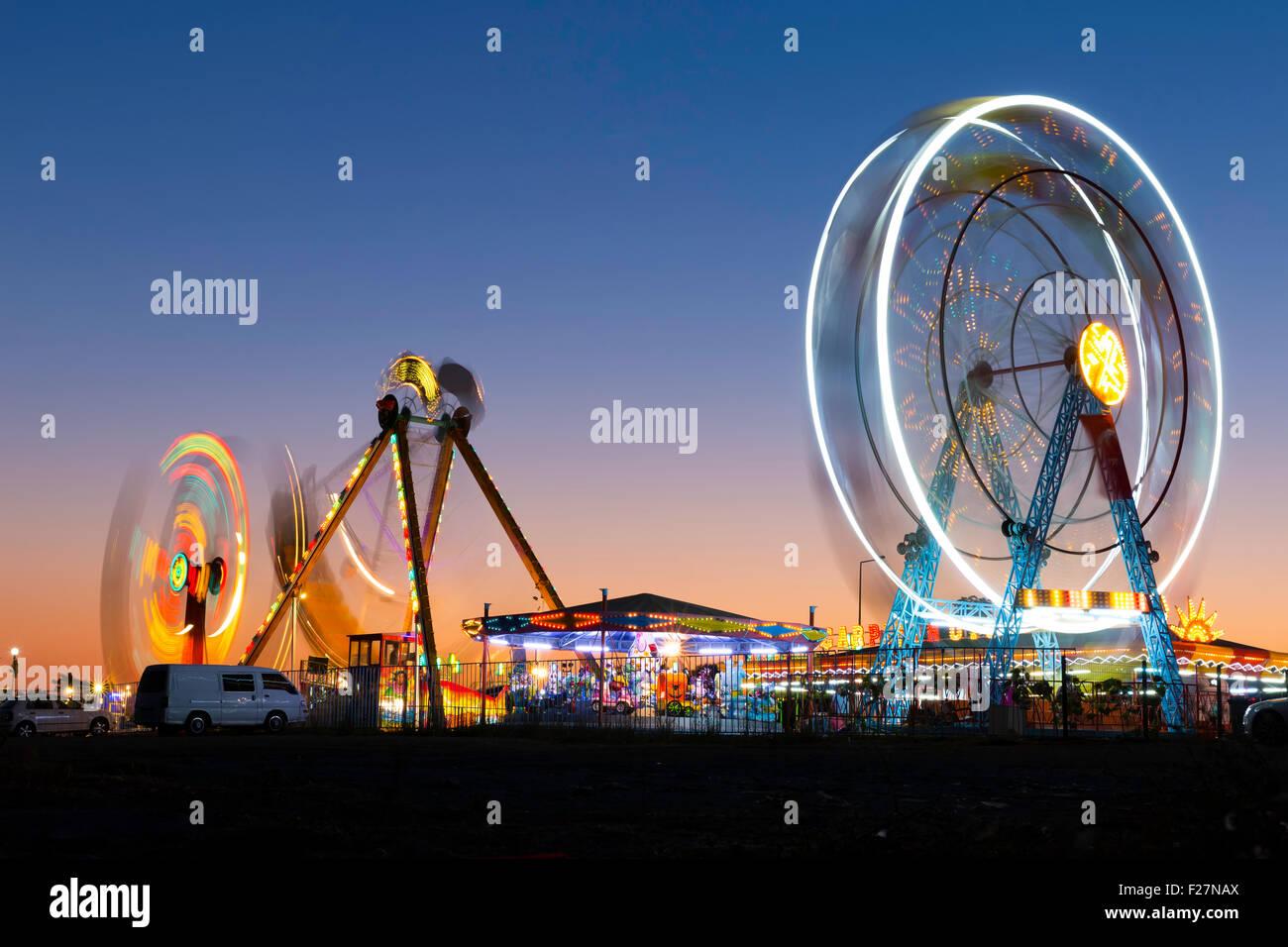 Colorido carnaval noria y la góndola spinning en movimiento borrosas al atardecer en un parque de diversiones Imagen De Stock