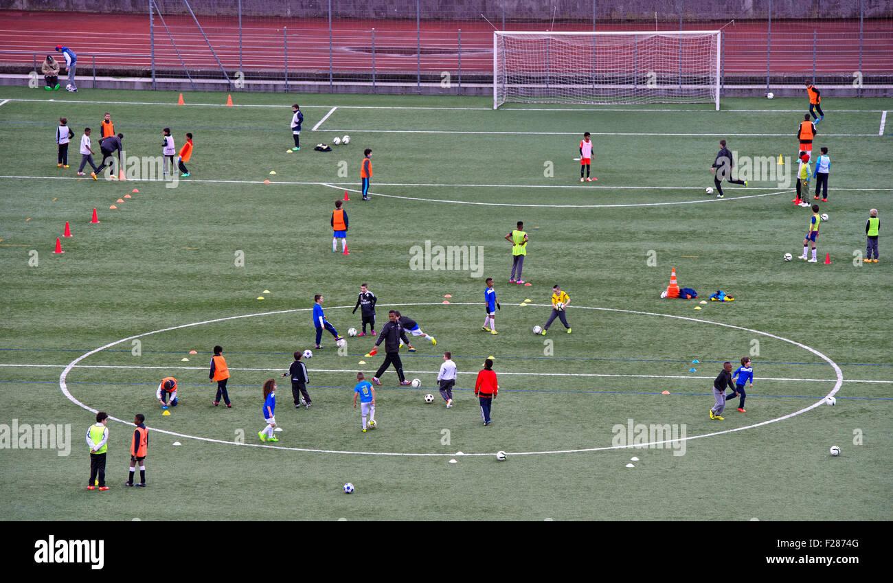 Los niños con ropas de colores en un campo de deportes, durante la práctica de fútbol, el Cantón Imagen De Stock