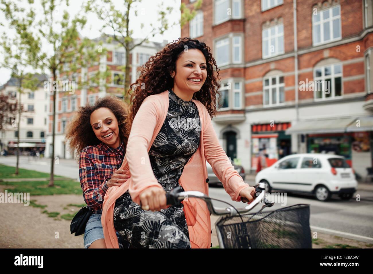 Retrato de alegres jóvenes amigos a montar una bicicleta en la ciudad. Las niñas al aire libre y disfrutar Imagen De Stock