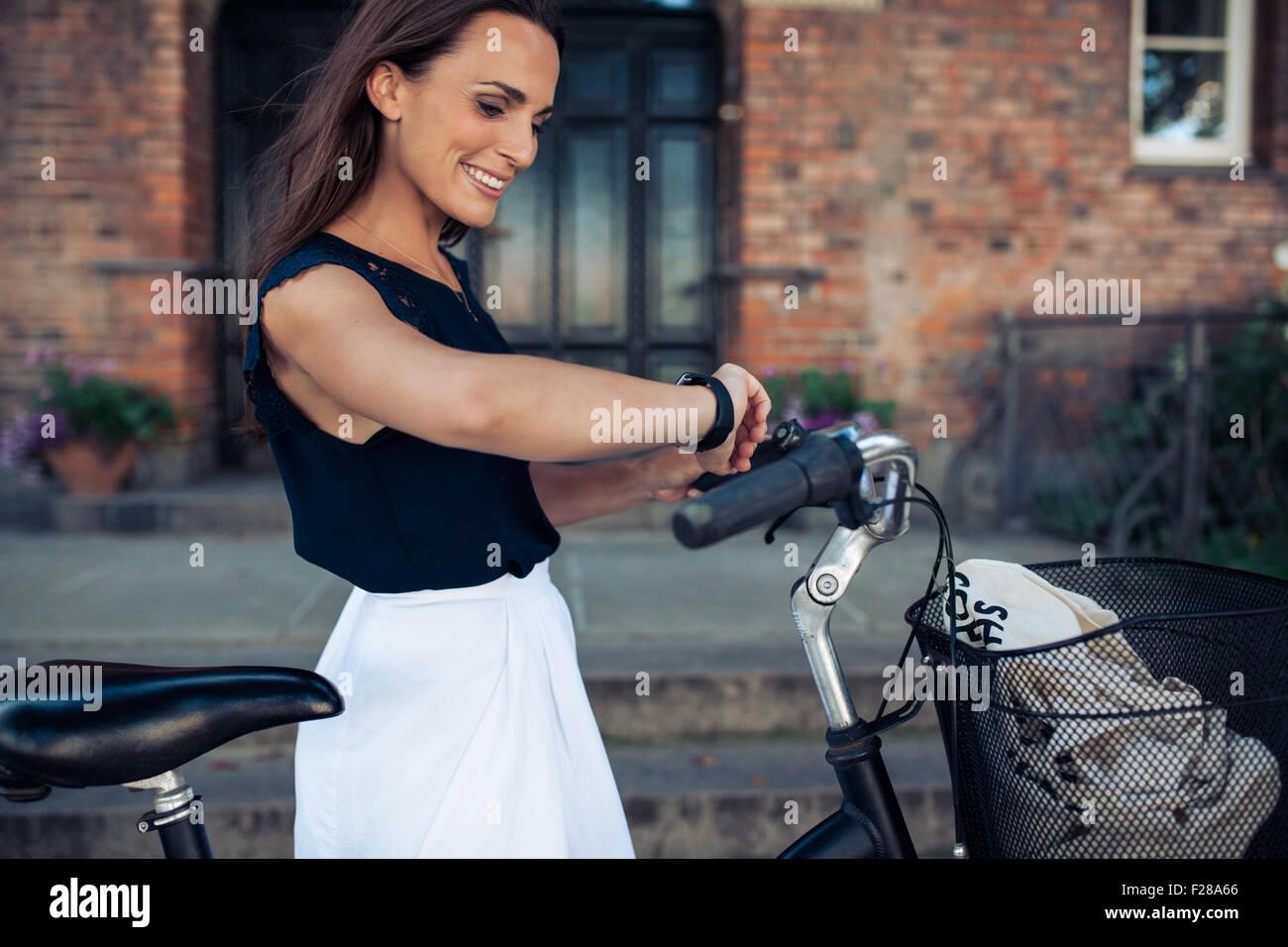 Mujer joven con una bicicleta comprobando la hora en su reloj de pulsera. Feliz mujer con bicicleta mirando a ver, Imagen De Stock