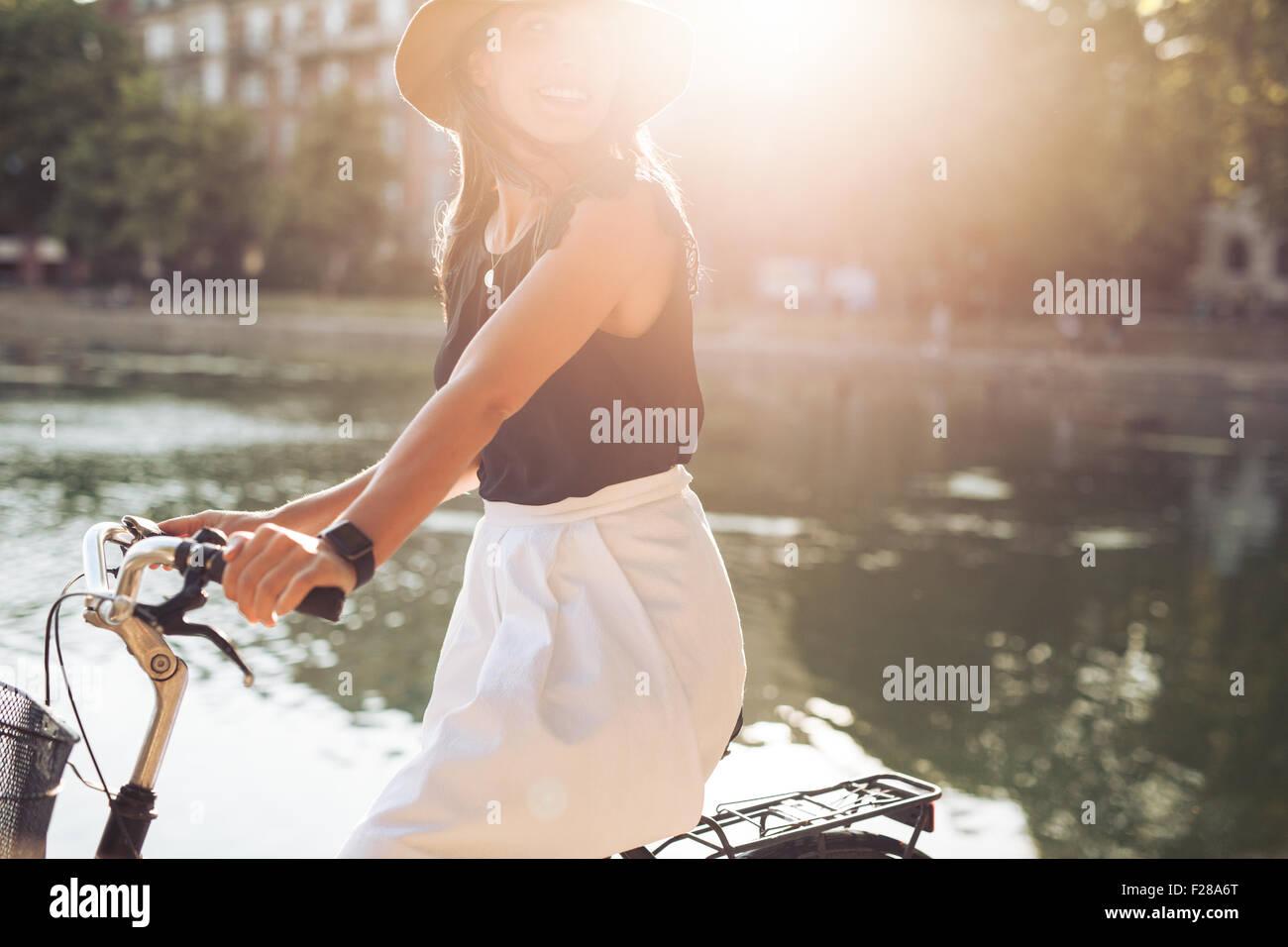 Retrato de mujer bastante joven montando en su bicicleta mirando a otro lado, sonriente, con la llamarada solar. Mujer ciclismo en un día de verano. Foto de stock