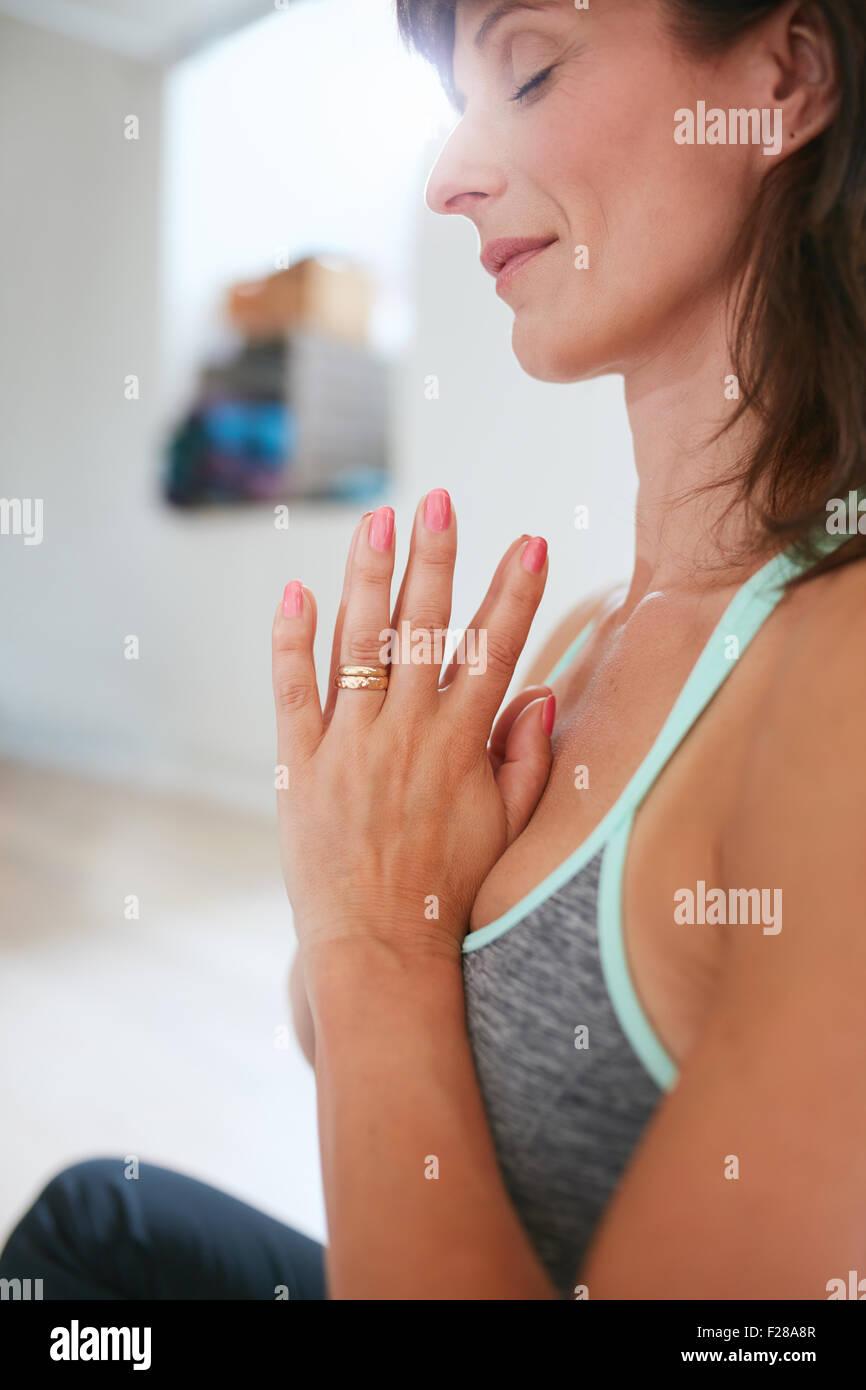 Vista lateral de la mujer practicando yoga sentado en posición de oración. Mujer meditando en pose de yoga. Foto de stock