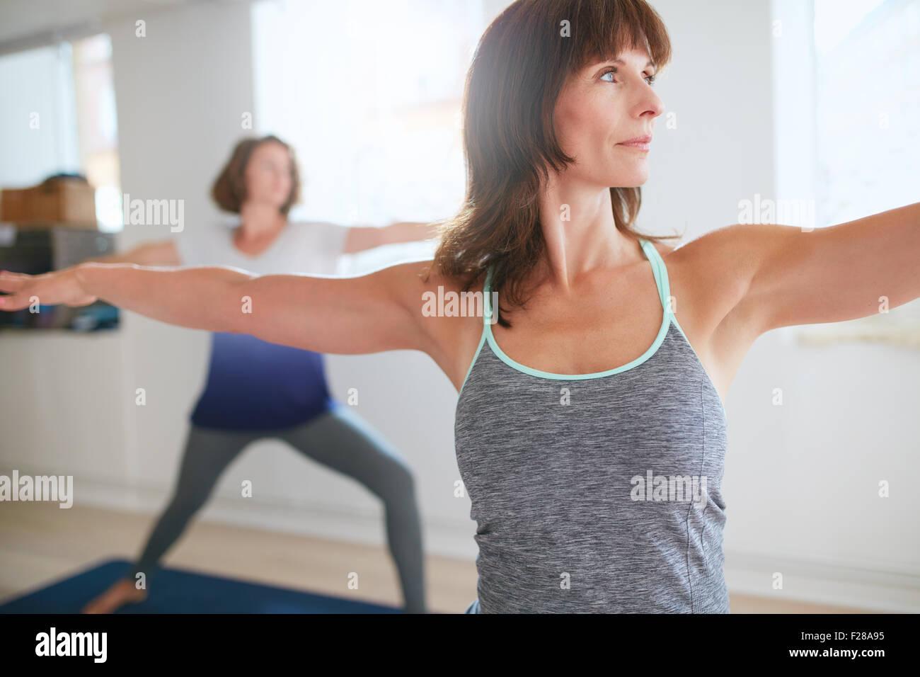 Fitness trainer haciendo el guerrero plantean durante la clase de yoga. Profesor de Yoga realizar Virabhadrasana Imagen De Stock