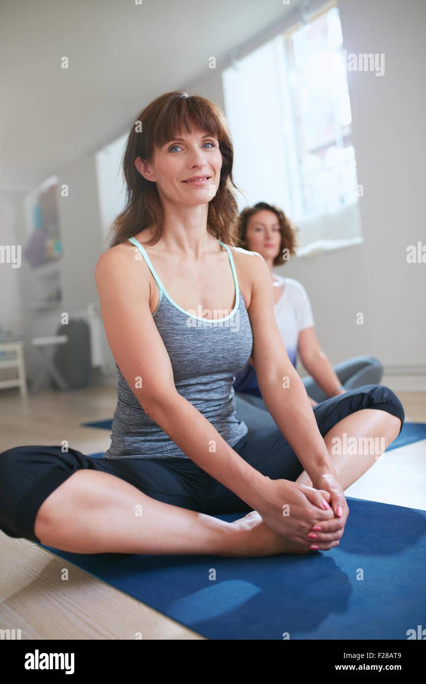 Retrato de mujer Fitness trainer sentado en el suelo Baddha konasana yoga pose. Mujer en la clase de yoga sentado Imagen De Stock