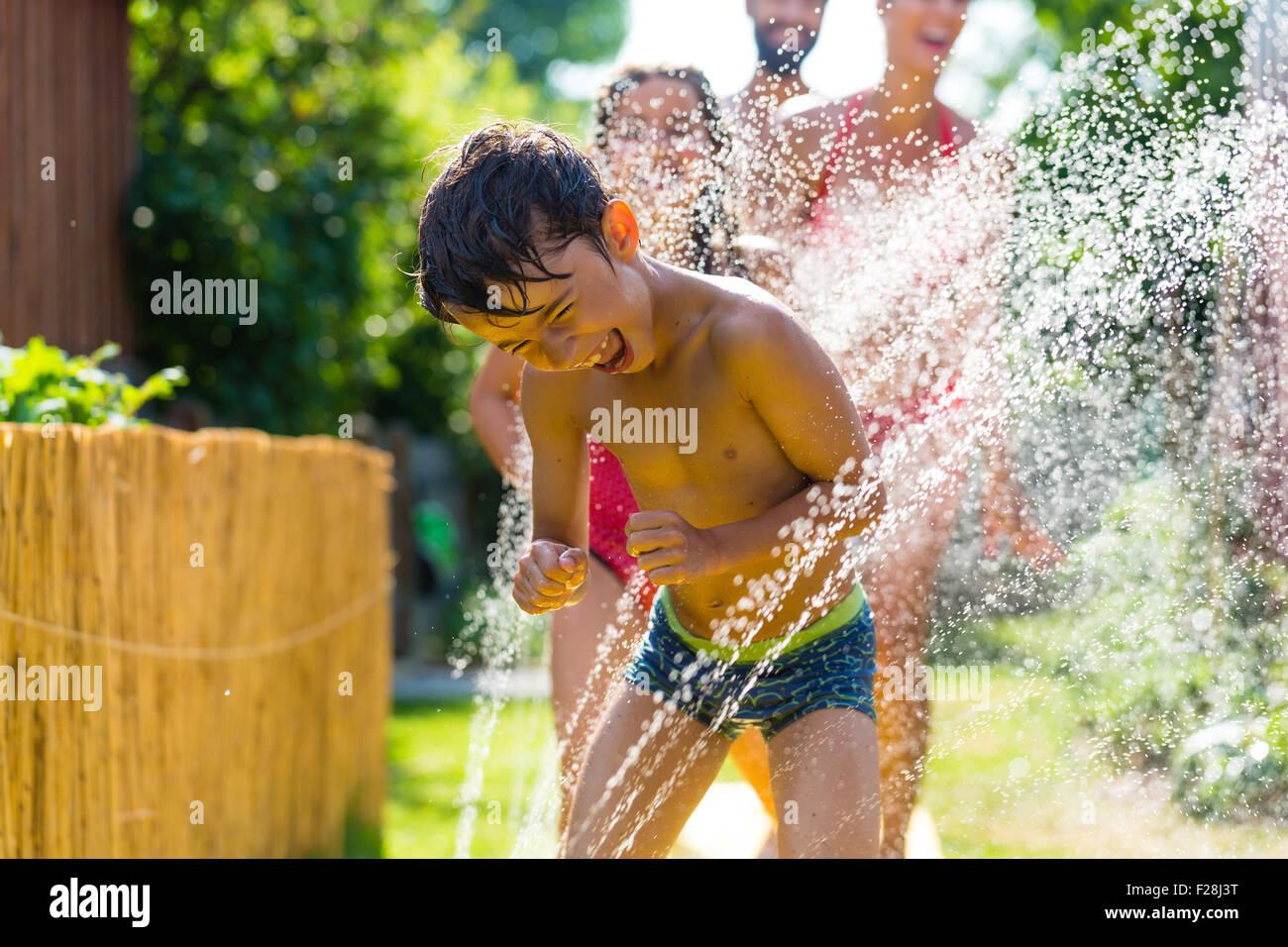 El enfriamiento de la familia con rociador en el jardín, un montón de agua salpicando alrededor Imagen De Stock