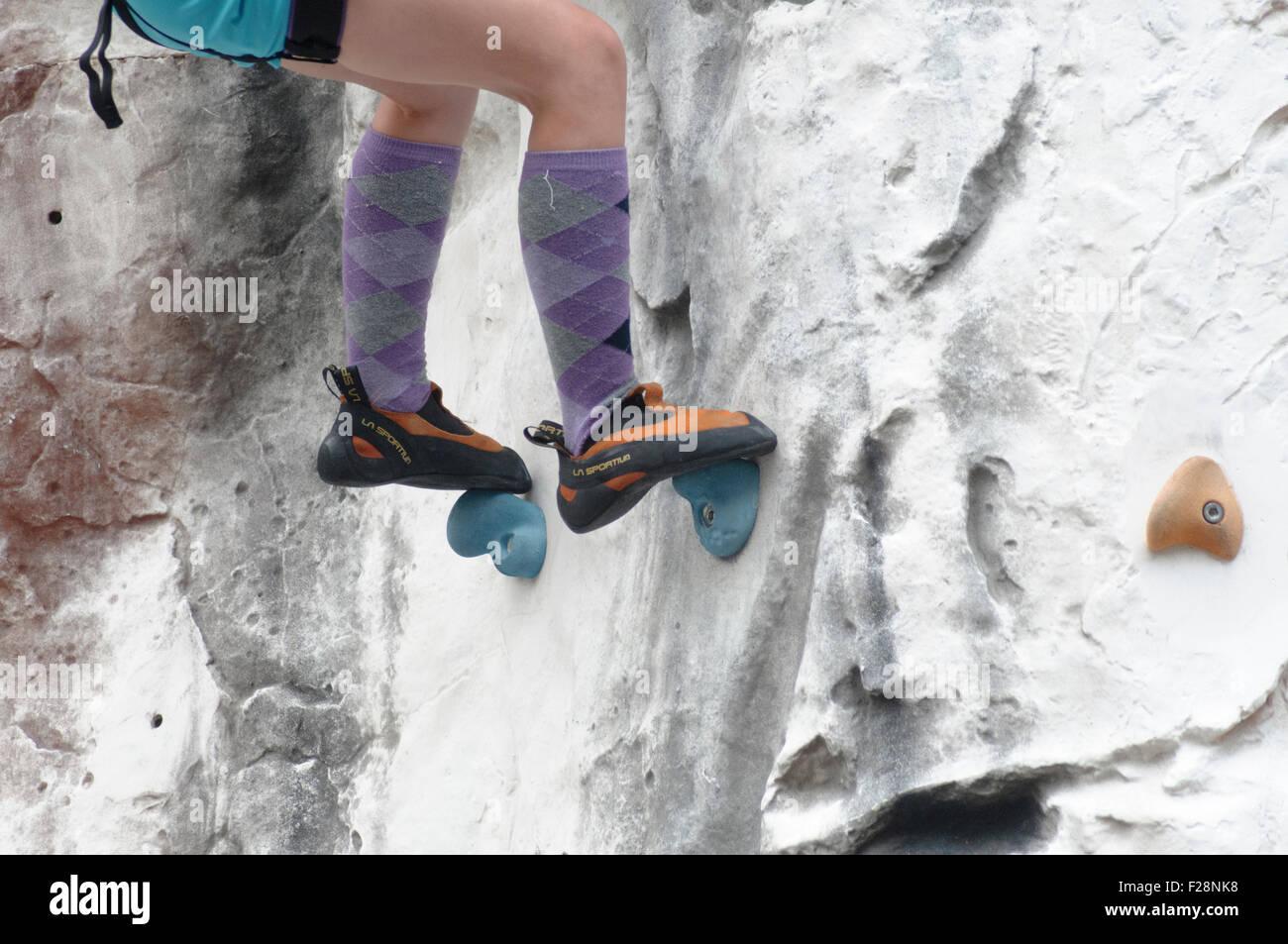 Adolescente chica sube un muro artificial de escalada cerca de los pies y los zapatos de escalada especial Imagen De Stock