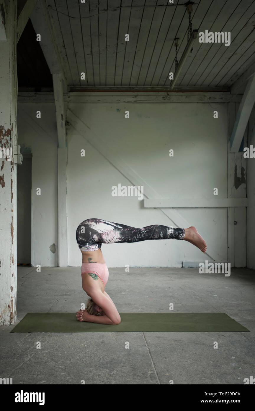 Mitad mujer adulta practicando hacer el pino pose de yoga studio, Munich, Baviera, Alemania Imagen De Stock