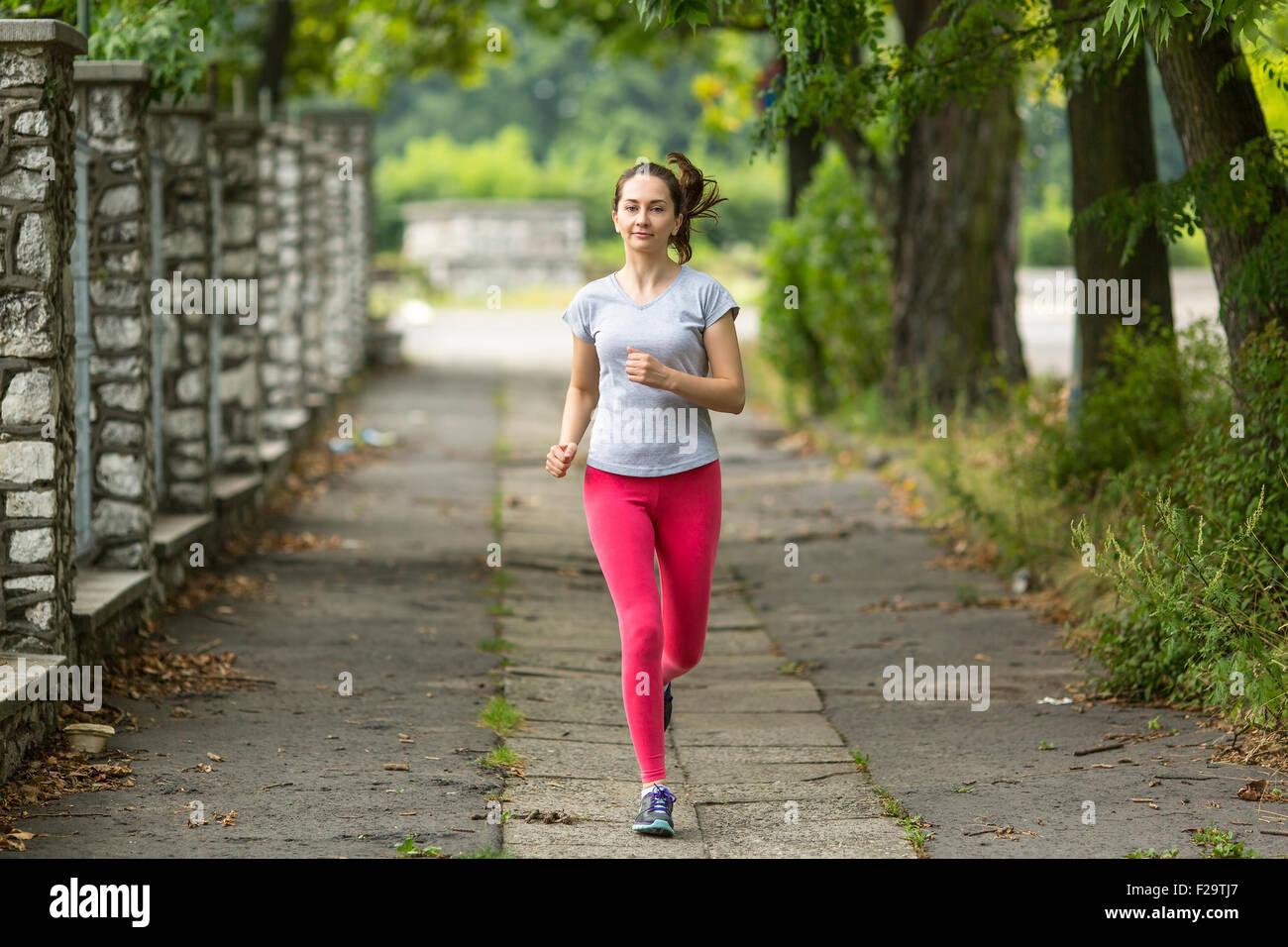 Ejecutando. Mujer joven jogging en el parque. Correr por la mañana. Estilo de vida saludable. Imagen De Stock