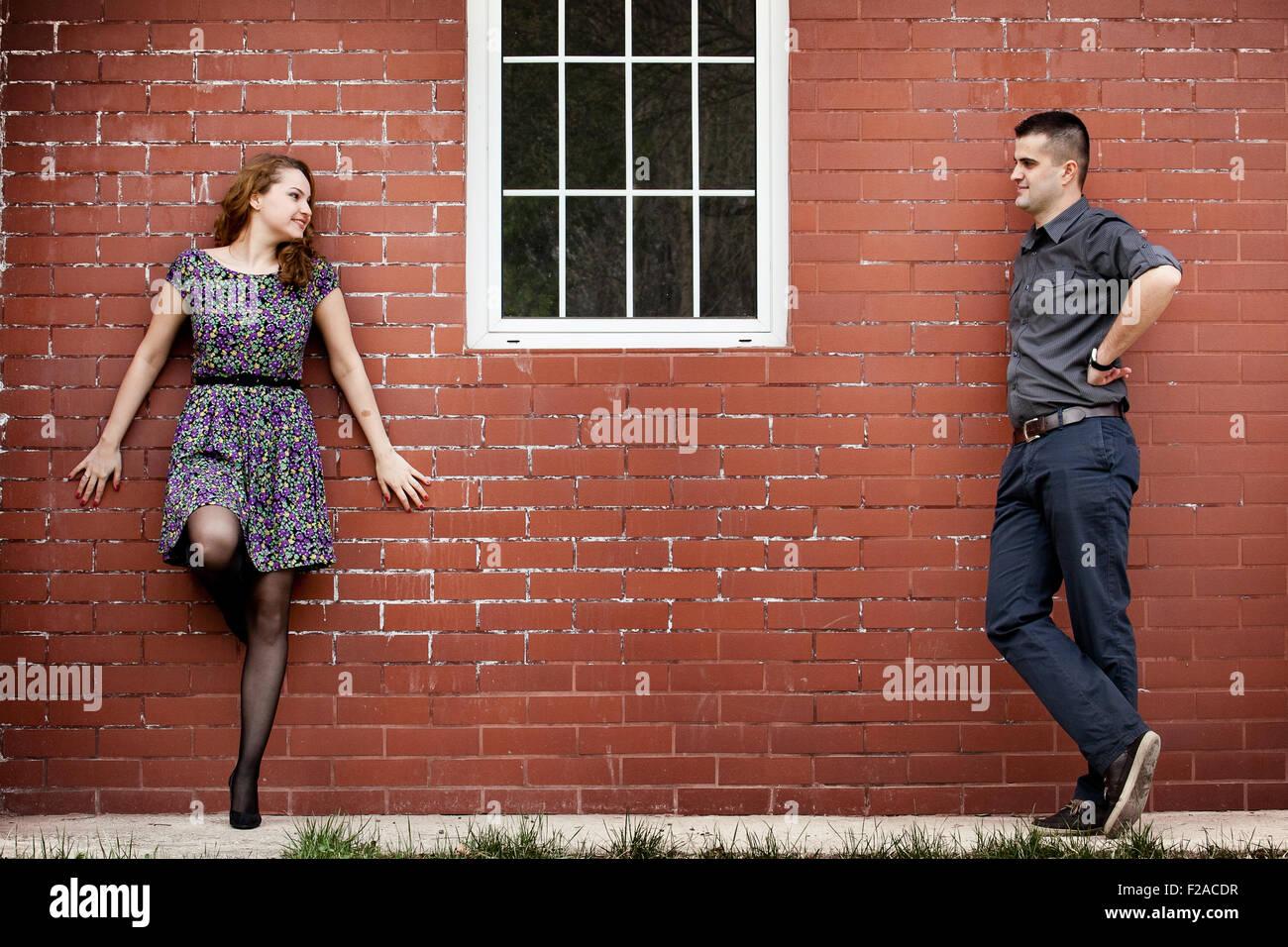 Feliz pareja joven y casa con pared de ladrillo Imagen De Stock