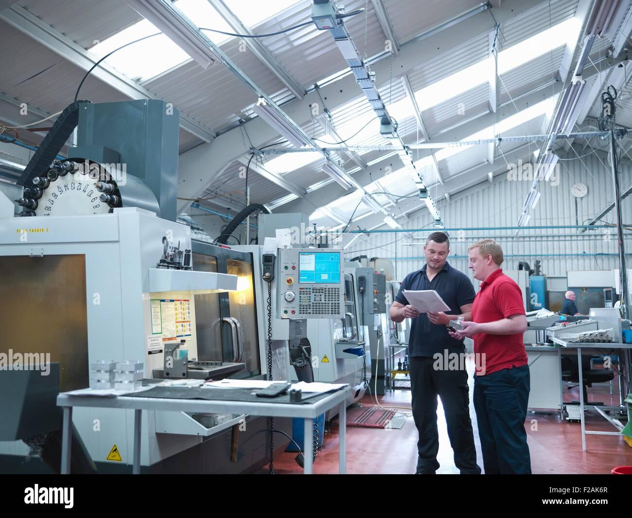 Ingenieros discutiendo trabajo delante de máquinas CNC en fábrica de ingeniería Imagen De Stock