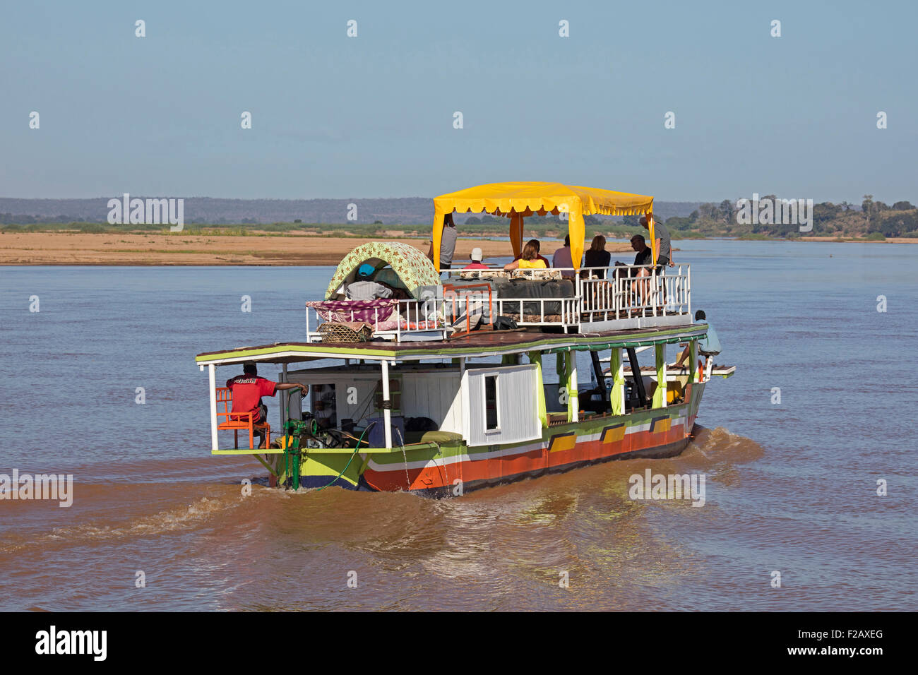 Motor a los turistas en un viaje en barco por el río Tsiribihina / Tsiribinha al atardecer en Menabe, Madagascar, Imagen De Stock