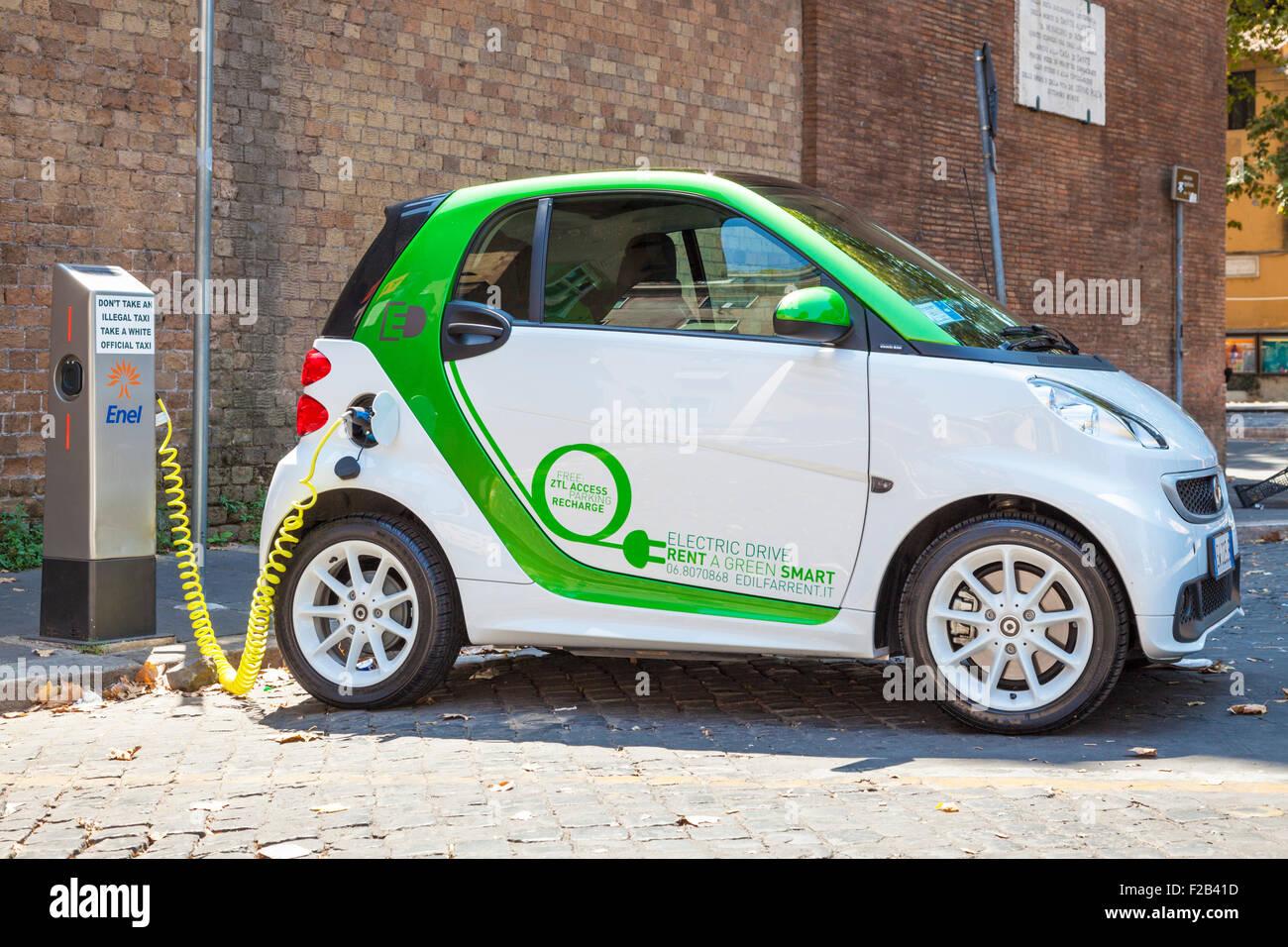 Smart fortwo electric drive coche eléctrico enchufado a un punto de carga de coches eléctricos en Roma Imagen De Stock