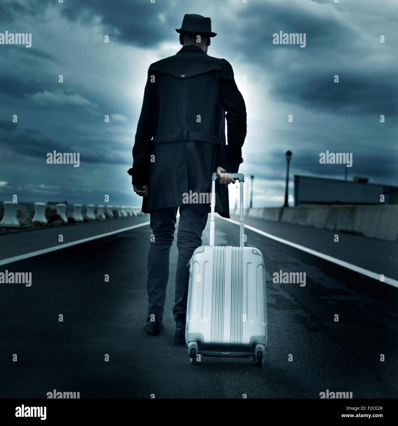 Primer plano de un joven hombre visto desde atrás llevando su maleta con ruedas, con un efecto dramático Imagen De Stock