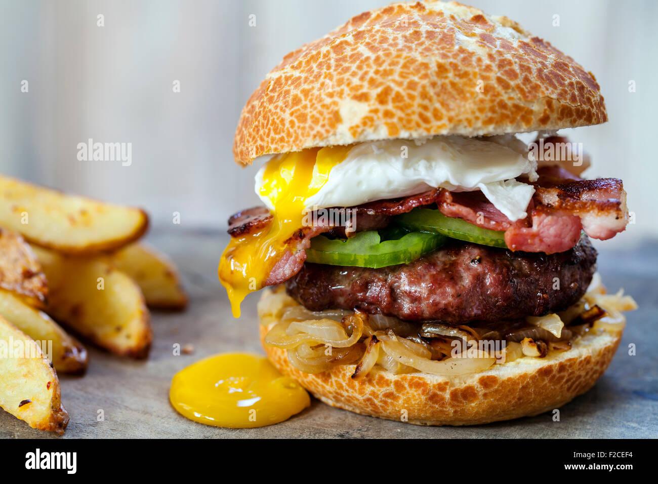 Hamburguesa de carne con tocino y huevos escalfados Imagen De Stock