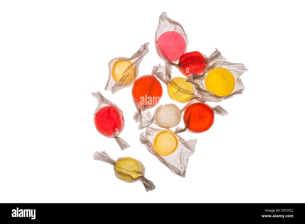 Vista aérea de naranja, amarillo, rojo, rosado en envoltorios de caramelos en la mesa de luz Imagen De Stock