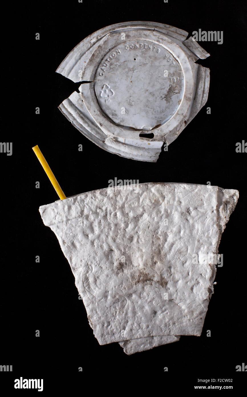 Styrofoam sucio aplanada de la taza de café con café amarillo agitador y tapa de plástico sucia sobre Imagen De Stock