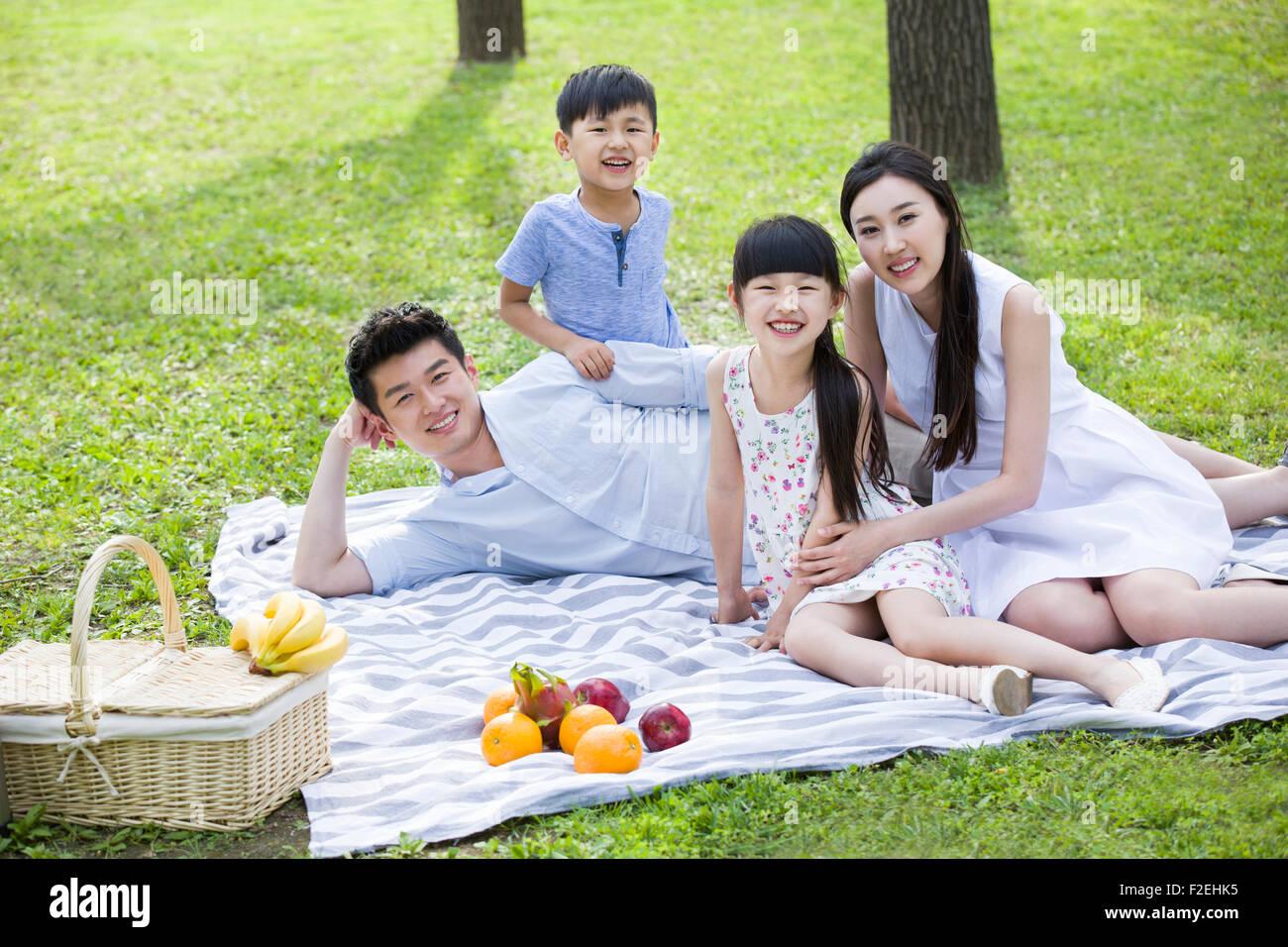 Feliz familia joven tener un picnic en la hierba Imagen De Stock