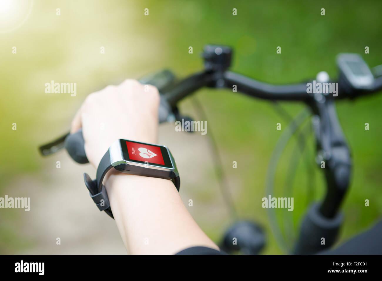 Mujer andar en bicicleta con un smartwatch monitor de ritmo cardíaco. Reloj inteligente concepto. Foto de stock