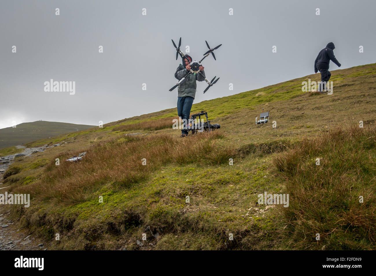 Preparación de un gran equipo de filmación caro filmar drone en la cima de una montaña en el distrito de los lagos Foto de stock