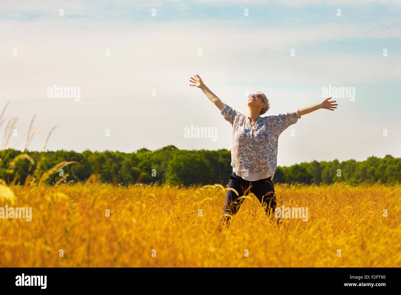 Exuberante mujer mayor con los brazos extendidos en el soleado campo rural Imagen De Stock