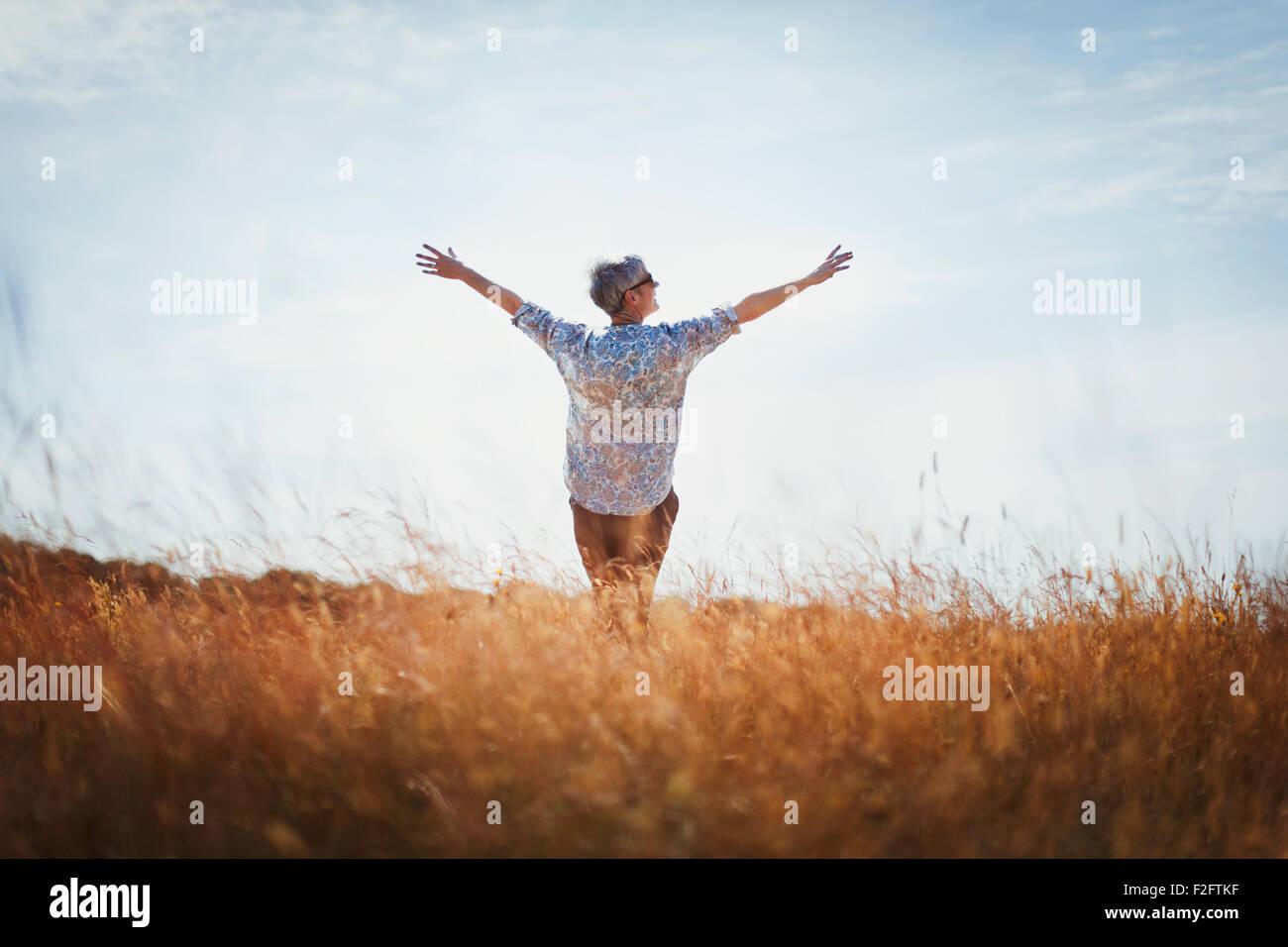 Exuberante mujer mayor con los brazos extendidos en un soleado día de campo Imagen De Stock