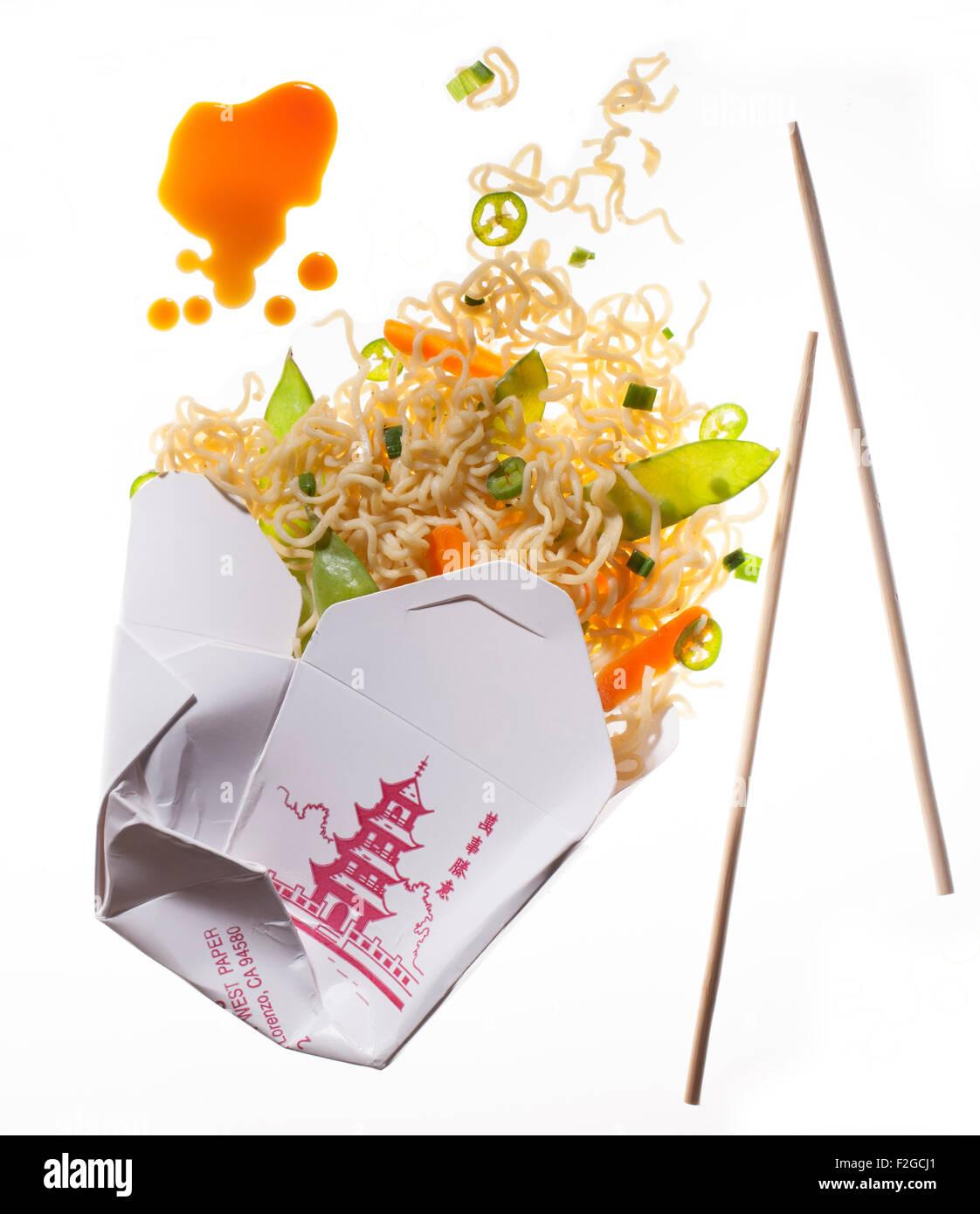 Fideos Chinos para ir saliendo del recipiente con salsa de soja y los palillos, iluminada desde atrás sobre blanco Foto de stock