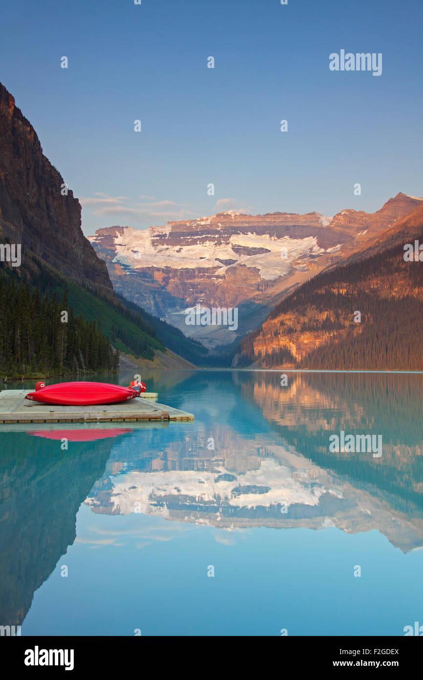 Rojo canoas a glacial Lake Louise con el glaciar Victoria, El Parque Nacional Banff, Alberta, Canadá Imagen De Stock