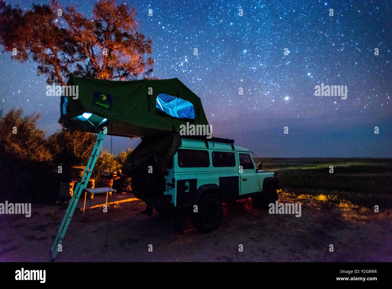 Land Rover aparcado con un pop-up tienda sobre su techo bajo el cielo nocturno en Botswana, África Foto de stock