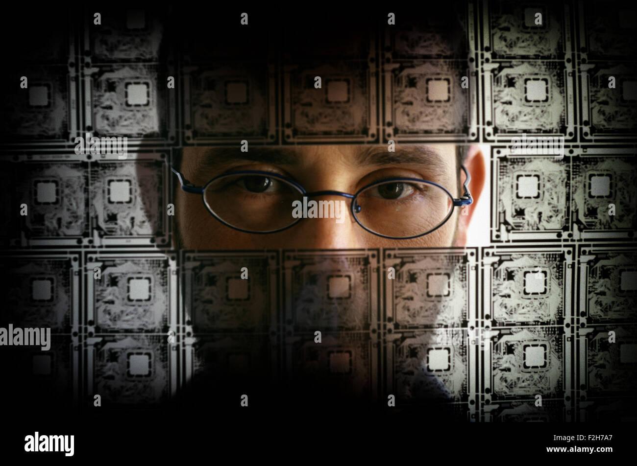 Una persona mirando a través de la placa de circuito eléctrico transparente y alambre de púas Imagen De Stock