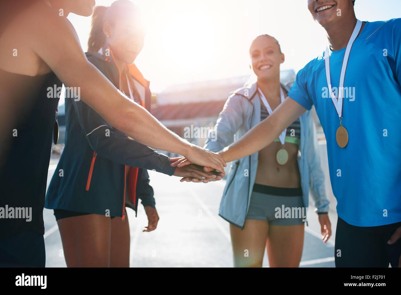 La foto de un grupo de jóvenes deportistas con medallas hinca sus manos mientras está de pie en un grupito. Imagen De Stock