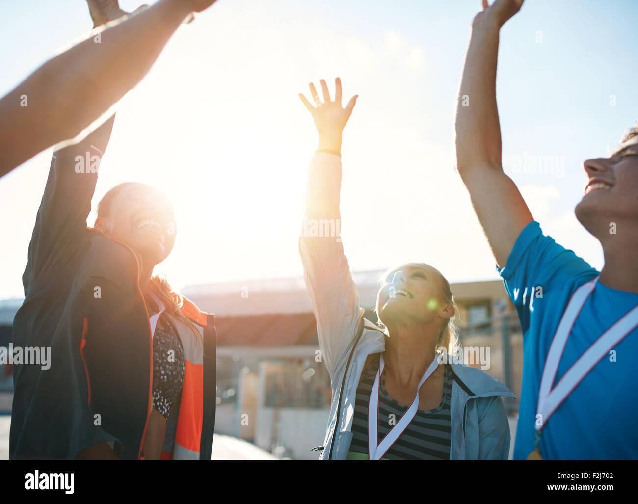 Grupo de atletas jóvenes celebrando el éxito mientras está de pie en un grupito. Equipo de atletas Imagen De Stock